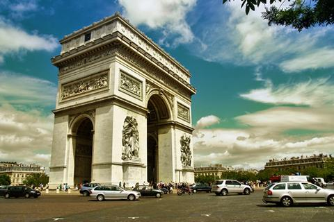 An image of the Arc de Triomphe with cars in the foreground.