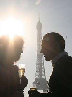 A couple enjoying a glass of champagne in the shadow of the Eiffel Tower in Paris.