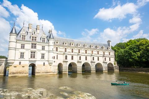 Two people in a row boat in front of Chenonceau castle in the Loire Valley, France.