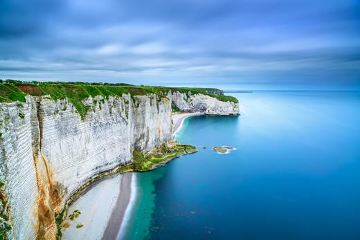 A birds-eye view of the white cliffs of Etretat and the beach below in Normandy, France.