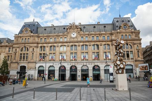 The front exterior of Gare St. Lazare rail station in Paris on a summer day.