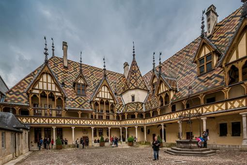 A tourist poses for a picture in the courtyard of the Hospices de Beaune, in Beaune, France.