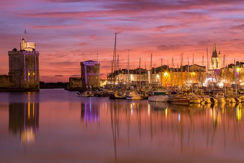 Poitou-Charentes: An image of La Rochelle from the harbor at sunset.
