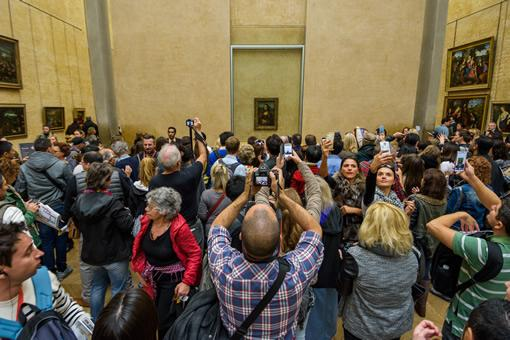 """Tourists crowd the """"Mona Lisa room"""" at the Louvre museum."""
