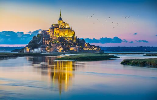 Mont St. Michel and the surrounding marshland at dusk.