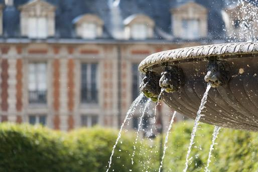 A fountain in the center of the Place des Vosges, Paris.