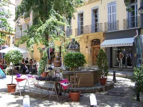 Empty chairs in a town square in Aix-en-Provence in summer.
