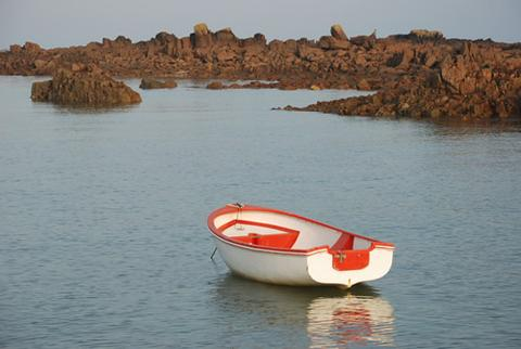 A row boat anchored along the Pink Granite Coast in Brittany, France.