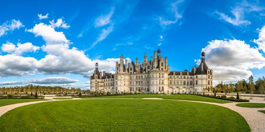 An image of the great lawn and exterior of Chambord Castle on a sunny day.