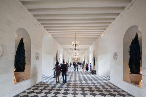 Tourists exploring an interior of Chenonceau Castle.