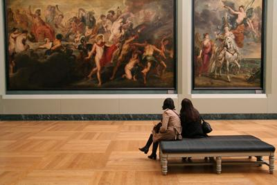 Two women take in an old painting Inside the Louvre museum in Paris.