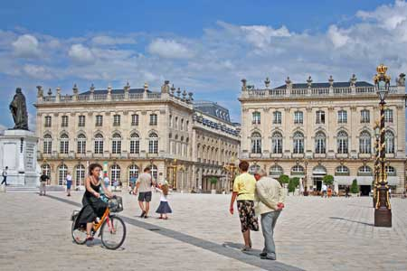 A woman riding a bike in the town center of Nancy, France.
