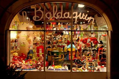 A view through the window of a small toy shop in Paris, France.