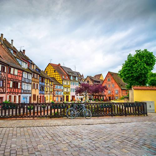 A bike tied up in front of a row of half-timbered houses in Colmar, France.