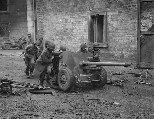 Soldiers moving artillery in Normandy after D-Day.