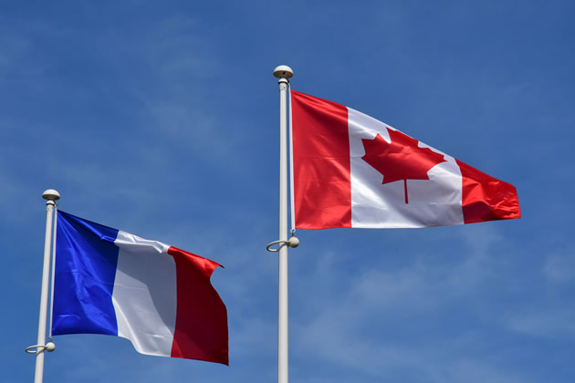 A Canadian and French flag flying together at Bernieres-sur-Mer.