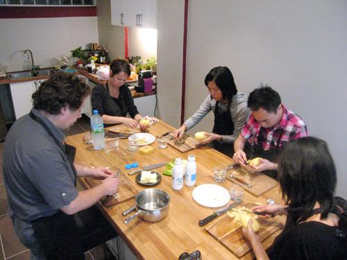 Students prep a meal at a cooking class in Paris.