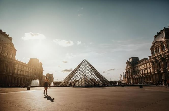 An early morning jogger runs near the Louvre in Paris, France.
