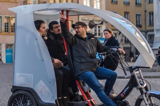 A pedicab driver points out a site of interest in the city of Lyon.